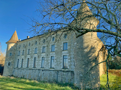 Impressive château built in the 14th and 18th centuries with outbuildings around a large swimming pool.